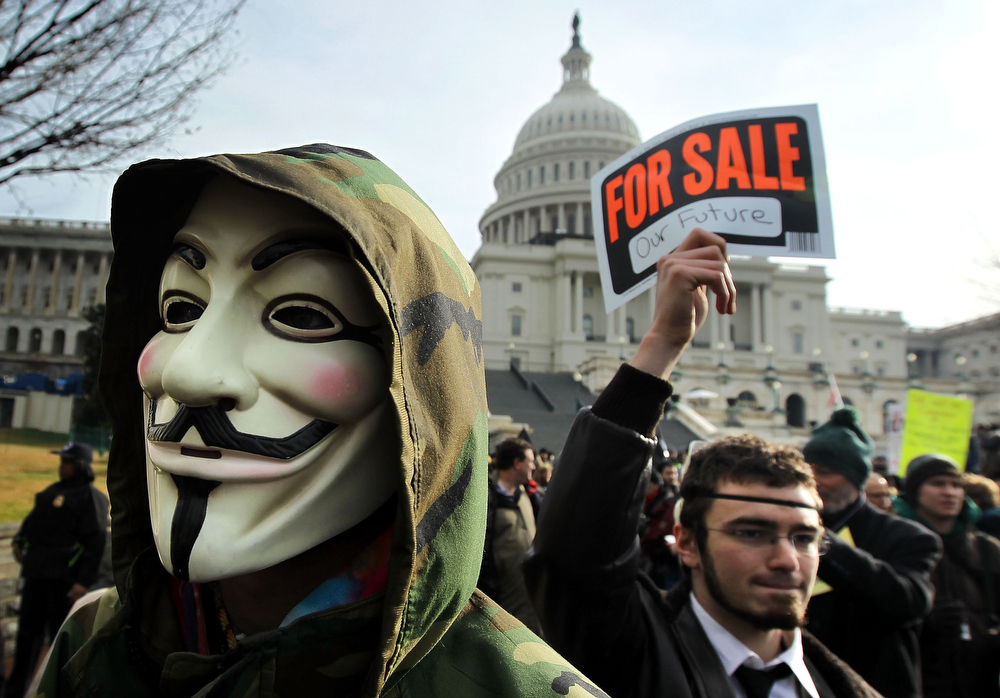 Description of . A demonstrator wears a Guy Fawkes mask during an