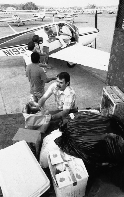 . Glen Ward, on wing, unloads his aircraft and passes relief supplies from man to a flatbed truck at the airport, Sunday, Oct. 23, 1989 Watsonville, Calif. (AP Photo/Douglas C. Pizac)