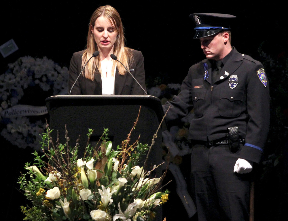 . Santa Cruz police detective Sgt. Loran \'Butch\' Baker\'s daughter Jillian speaks as his son Adam provides support during Baker\'s memorial service at HP Pavilion Thursday. (Shmuel Thaler/Sentinel)
