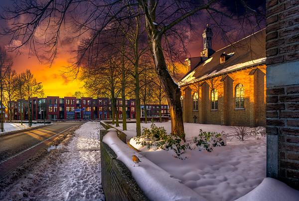 Fine Art architectuur foto van de Sint Lambertus kerk te Nistelrode in de winter met sneeuw en kale bomen aan het Laar met een roodborstje op de muur en Laarstede en de kruising met Maxend op de achtergrond.