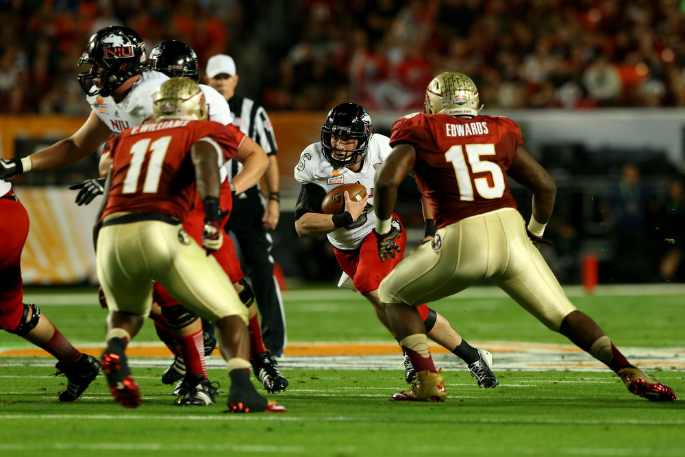 Description of . Quarterback Jordan Lynch #6 of the Northern Illinois Huskies runs with the ball in the first half against the Florida State Seminoles during the Discover Orange Bowl at Sun Life Stadium on January 1, 2013 in Miami Gardens, Florida.  (Photo by Mike Ehrmann/Getty Images)