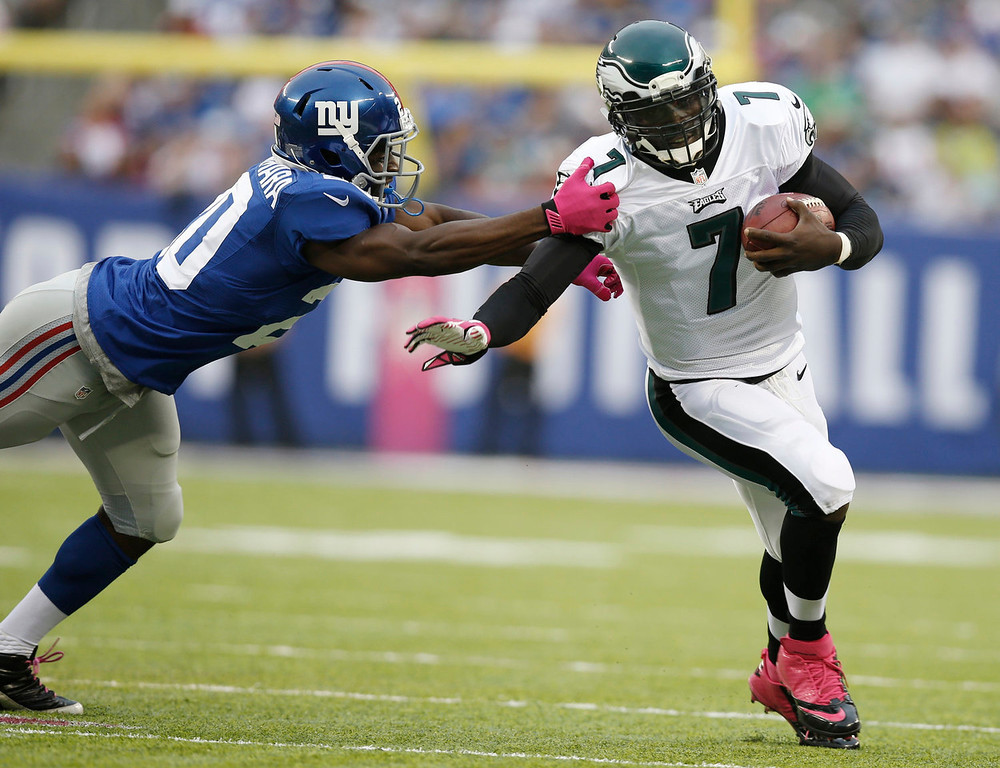 . Philadelphia Eagles quarterback Michael Vick (7) breaks a tackle by New York Giants cornerback Prince Amukamara (20) during the first half of an NFL football game Sunday, Oct. 6, 2013, in East Rutherford, N.J.  (AP Photo/Kathy Willens)