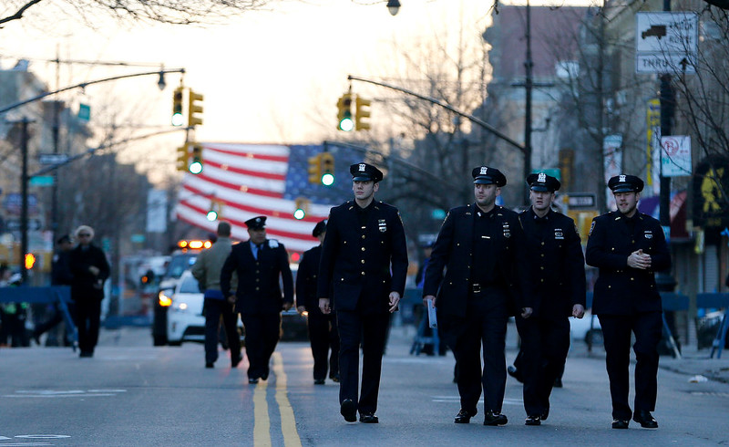 . New York City police officers walk toward Christ Tabernacle Church before funeral services for officer Rafael Ramos at in the Glendale section of Queens, Saturday, Dec. 27, 2014, in New York. Ramos and his partner, officer Wenjian Liu, were killed Dec. 20 as they sat in their patrol car on a Brooklyn street. The shooter, Ismaaiyl Brinsley, later killed himself. (AP Photo/Julio Cortez)