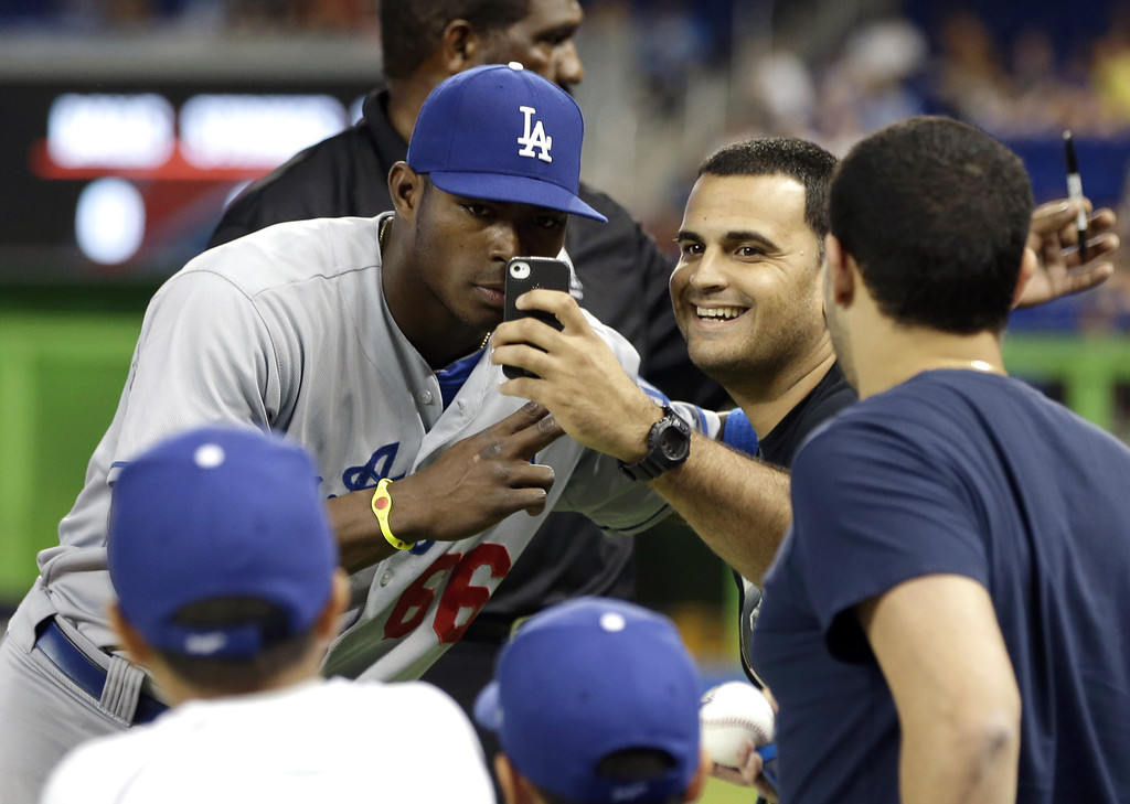 . Los Angeles Dodgers right fielder Yasiel Puig, left, poses for a photo with a fan before  a baseball game against the Miami Marlins, Monday, Aug. 19, 2013, in Miami. (AP Photo/Lynne Sladky)