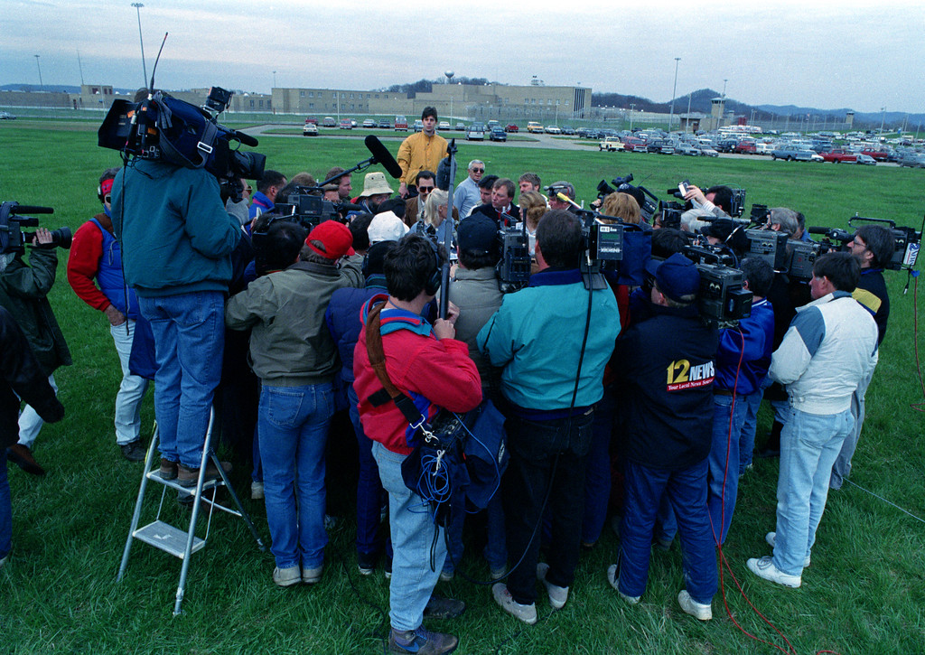 . Reporters and photographers surround a prison spokesperson during a news conference outside the Southern Ohio Correctional Facility, background, in Lucasville, Ohio, April 13, 1993. Seven prisoners have been killed and eight guards taken hostage during the prison siege that began April 11, Easter Sunday. (AP Photo/Gary Gardiner)