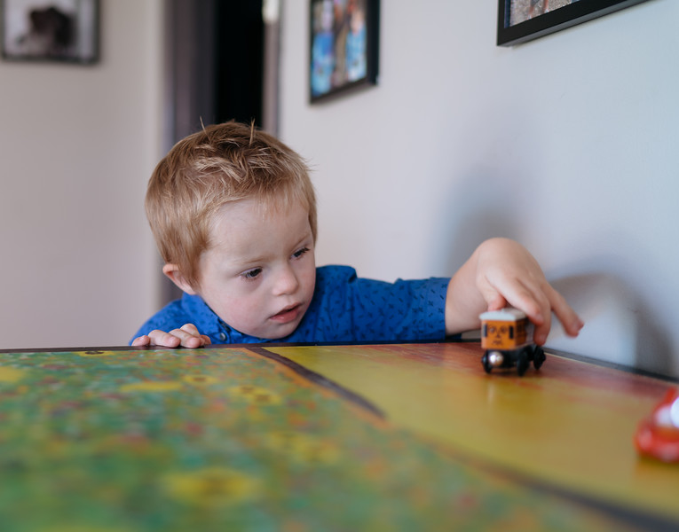 Preschooler playing with a toy train at home