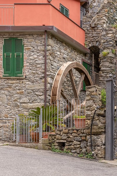 a waterwheel in a stone wall in Manarola, Italy