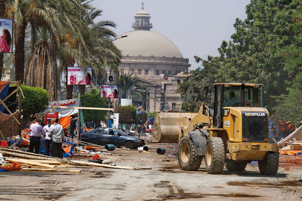 . A bulldozer removes debris after security forces cleared the smaller camp of supporters of deposed Egyptian President Mohammed Morsi, in front of Cairo University, Giza, Cairo, Egypt, Wednesday, Aug. 14, 2013.  Egyptian police in riot gear swept in with armored vehicles and bulldozers Wednesday to clear the sit-in camps set up by supporters of the country\'s ousted Islamist president in Cairo, showering protesters with tear gas as the sound of gunfire rang out. (AP Photo/ Ahmed Abd El Latif, El Shorouk Newspaper)