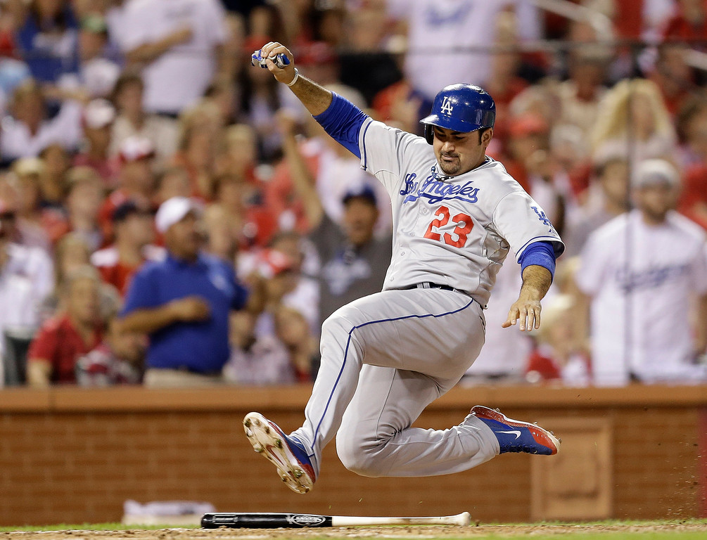 . Los Angeles Dodgers\' Adrian Gonzalez slides safely home after scoring on a two-run single by Juan Uribe during the third inning of Game 1 of the National League baseball championship series against the St. Louis Cardinals, Friday, Oct. 11, 2013, in St. Louis. (AP Photo/Jeff Roberson)