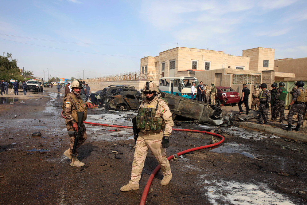 Description of . Civilians and security forces personnel gather at the scene of a car bomb attack in Baghdad, Iraq, Friday, March 29, 2013. A string of bombings targeting Shiite mosques on Friday, killing and wounding dozens of people, police said.(AP Photo/Karim Kadim)