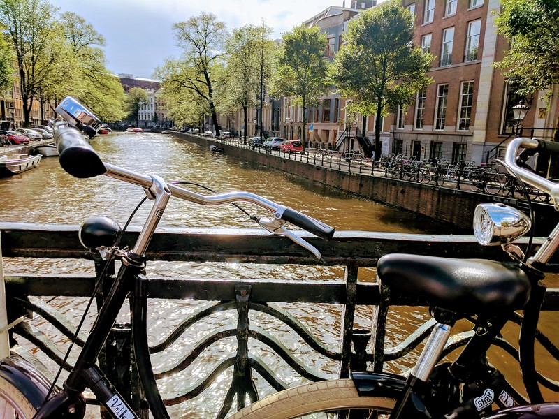 Bicycle parked near a canal on a self guided Amsterdam walking tour