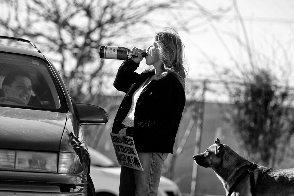 . A friend shares a bottle with Dorothy as he drives into the parking lot.