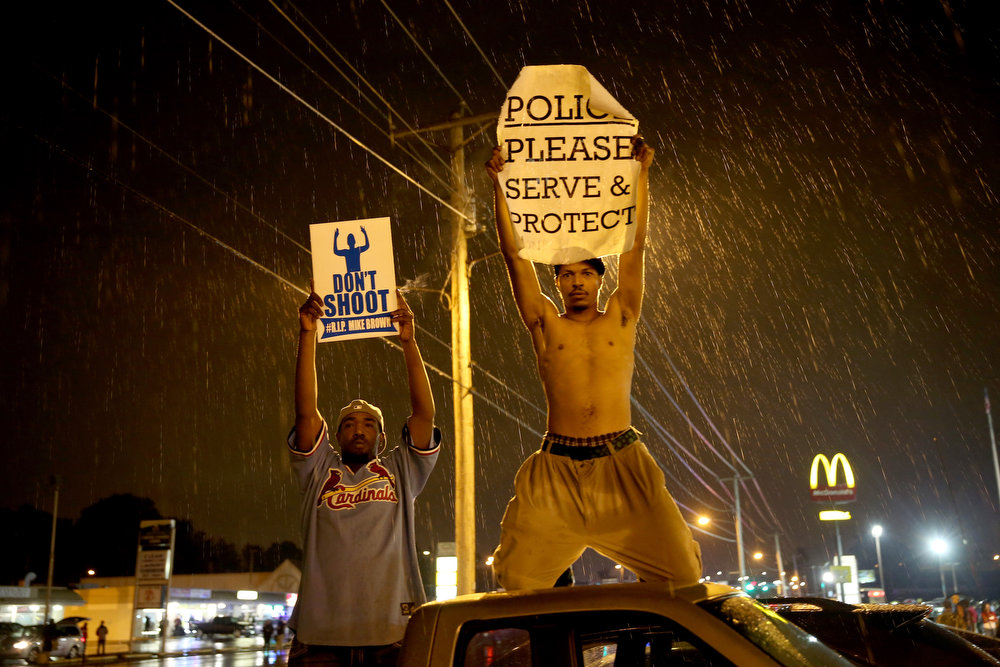. Demonstrators protesting the shooting death of Michael Brown hold signs on August 16, 2014 in Ferguson, Missouri. Violent outbreaks have taken place in Ferguson since the shooting death of Michael Brown by a Ferguson police officer on August 9th. (Photo by Joe Raedle/Getty Images)