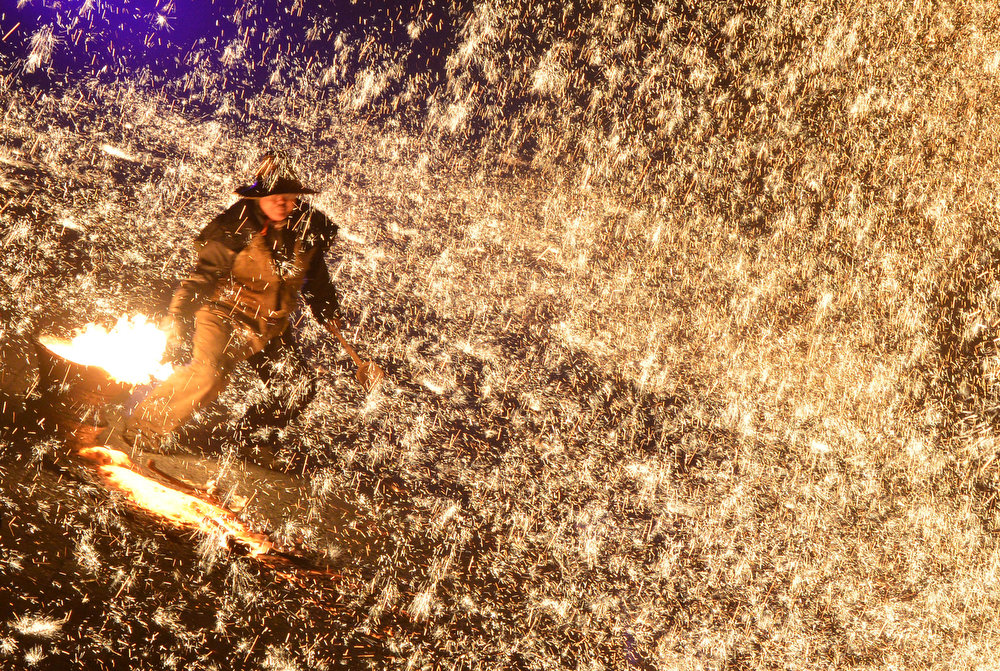 Description of . A Chinese blacksmith throws molten metal against a cold stone wall to create sparks, during the Lantern Festival which traditionally marks the end of the Lunar New Year celebrations, in Nuanquan, Hebei province on February 24, 2013.  For over 300 years, the village which is famous for its blacksmith skills, has maintained the tradition which they considered a cheaper alternative than buying fireworks during the Lantern Festival.       MARK RALSTON/AFP/Getty Images