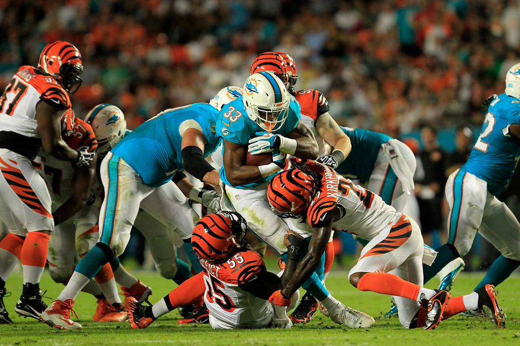 . MIAMI GARDENS, FL - OCTOBER 31:  Daniel Thomas #33 of the Miami Dolphins is tackled by Dre Kirkpatrick #27 of the Cincinnati Bengals at Sun Life Stadium on October 31, 2013 in Miami Gardens, Florida.  (Photo by Chris Trotman/Getty Images)