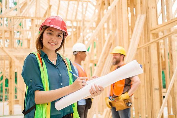 Female, Latin descent engineer, foreperson, or inspector checks blueprints inside a construction job site.  Other construction workers in background.   The multi-ethnic team is working inside an unfinished framed house or small commercial building.  They are wearing safety vests and hard hats.
