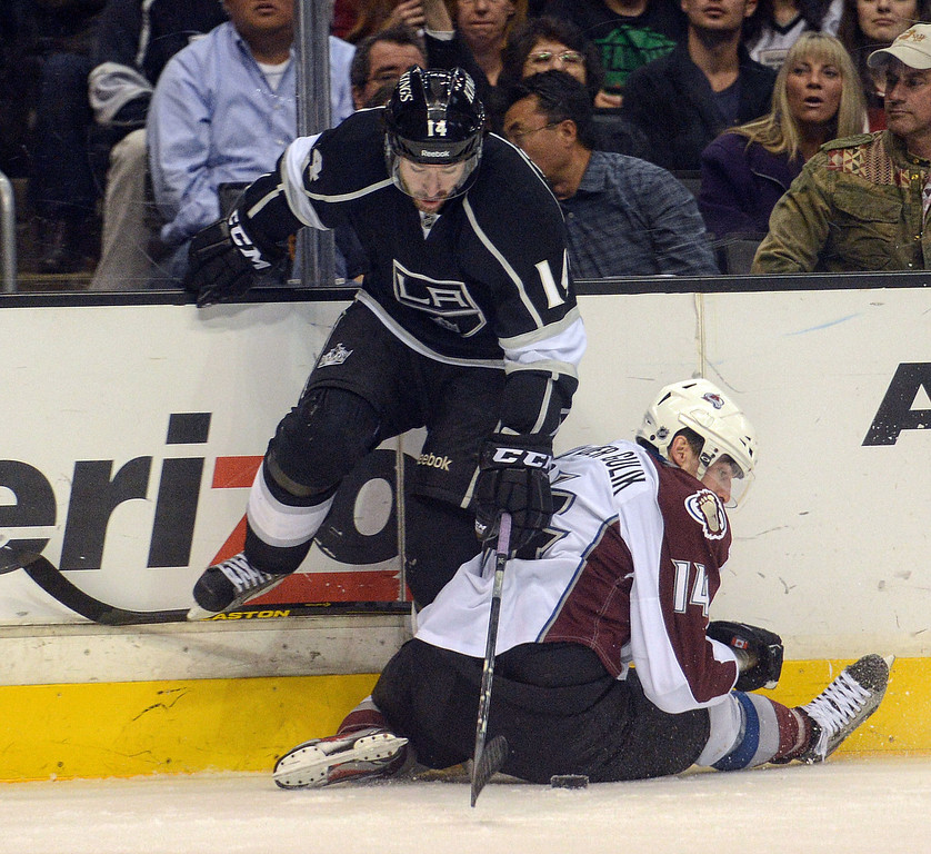 . The Kings\' Justin Williams #14 and the Avalanche\'s  David van der Gulik #14 battle for the puck against the boards during their game at the Staples Center in Los Angeles Thursday, April 11, 2013.(Hans Gutknecht/Staff Photographer)