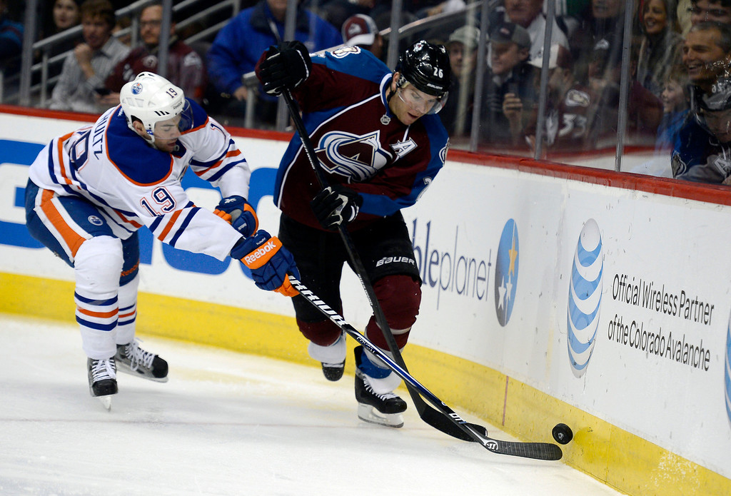 . Paul Stastny (26) of the Colorado Avalanche controls the puck around the boards as Justin Schultz (19) of the Edmonton Oilers comes in to poke it away during the first period March 12, 2013 at Pepsi Center. (Photo By John Leyba/The Denver Post)