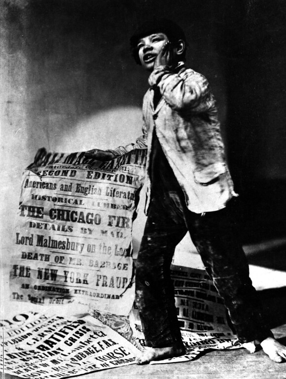 . 9th October 1871:  A young news vendor holding a poster announcing the Chicago Fire.  (Photo by Oscar Gustav Rejlander/Hulton Archive/Getty Images)