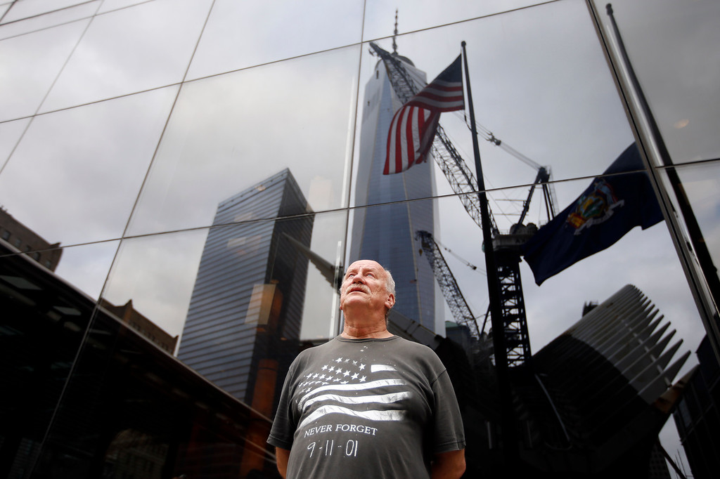 . 1 World Trade Center is reflected in the side of a building as Tyrone McClave, of Bristol, Penn., looks up at it during a moment of silence on the 13th anniversary of the Sept. 11, 2001 attacks, Thursday, Sept. 11, 2014, in New York. (AP Photo/Jason DeCrow)
