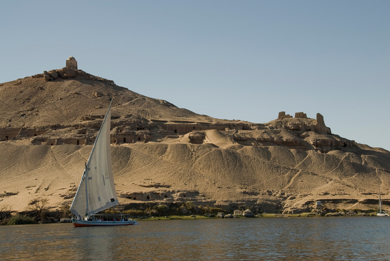 Felucca against sand cliff along Nile River- Aswan, Egypt