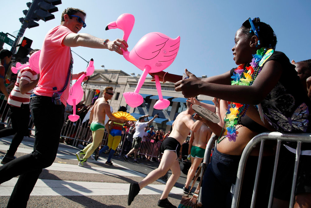 . A participant gives an inflatable pink flamingo to a girl in the crowd during the gay-pride themed Capital Pride Parade in Washington, June 8, 2013. REUTERS/Jonathan Ernst