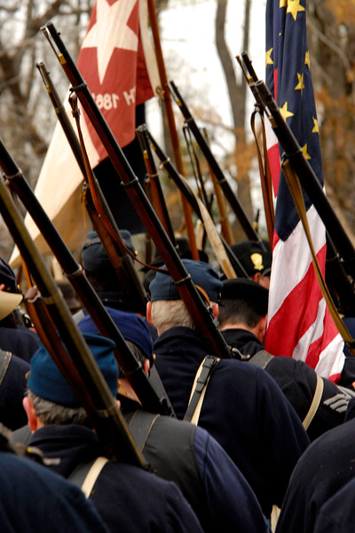 One of the South Carolina infantry flags flies next to the American flag as the reenactors march off the battlefield. The Skirmish at Gamble's Hotel happened on March 5, 1885 when 500 federal soldiers, under the command of Reuben Williams of the 12th Indiana Infantry, marched into Florence to destroy the railroad depot but were met by Confederate soldiers backed up with 400 militia. The reenactment, held by the 23rd South Carolina Infantry, was held at the Rankin Plantation in Florence, South Carolina on Saturday, March 5, 2011. Photo Copyright 2011 Jason Barnette