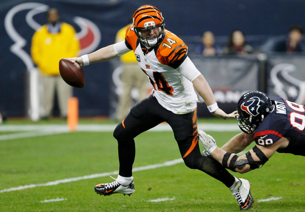 Description of . Cincinnati Bengals quarterback Andy Dalton (L) is pressured by Houston Texans defensive end J.J. Watt during the third quarter of their NFL AFC wildcard playoff football game in Houston, Texas January 5, 2013. REUTERS/Tim Sharp
