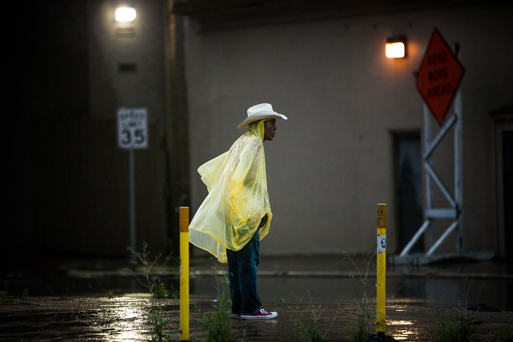 . AUSTIN, TX - MAY 25:   David Lopez waits to cross the street as rain falls on May 25, 2015 in Austin, Texas. Texas Gov. Greg Abbott toured the damage zone where one person is confirmed dead and at least 12 others missing in flooding along the Rio Blanco, which reports say rose as much as 40 feet in places, caused by more than 10 inches of rain over a four-day period. The governor earlier declared a state of emergency in 24 Texas counties.  (Photo by Drew Anthony Smith/Getty Images)