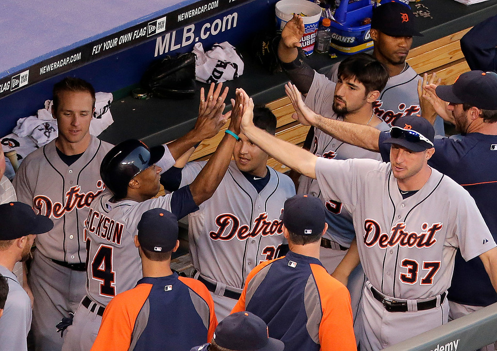 . Teammates celebrate with Austin Jackson (14) in the dugout after he scored on a two RBI double by Miguel Cabrera during the fourth inning of a baseball game Thursday, July 10, 2014, in Kansas City, Mo. (AP Photo/Charlie Riedel)