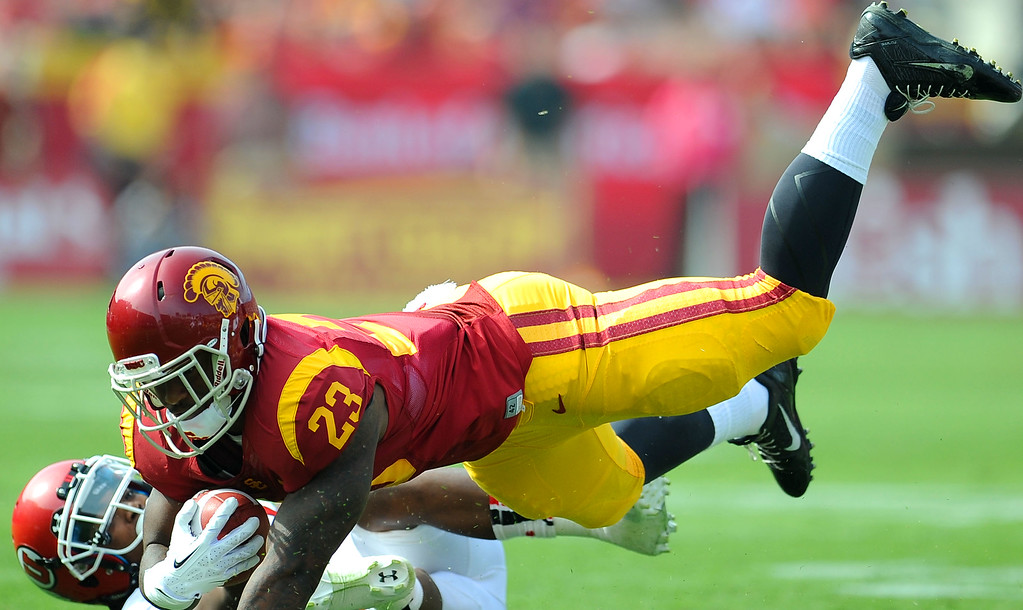 . Southern California running back Tre Madden (23) dives over Utah defensive back Justin Thomas (12) fir a first down during the first half of an NCAA college football game in the Los Angeles Memorial Coliseum in Los Angeles, on Saturday, Oct. 26, 2013.  (Photo by Keith Birmingham/Pasadena Star-News)