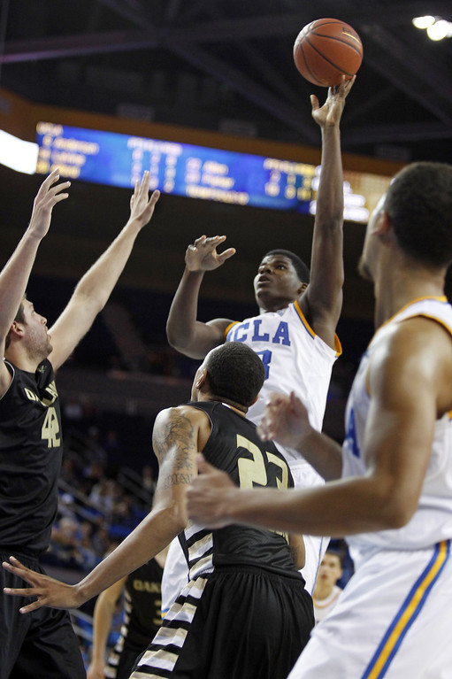 . UCLA center Tony Parker shoots over Oakland forward Corey Petros, left, and forward Tommie McCune (23) in the second half of their NCAA college basketball game Tuesday, Nov. 12, 2013, in Los Angeles. UCLA won the game 91-60.  (AP Photo/Alex Gallardo)