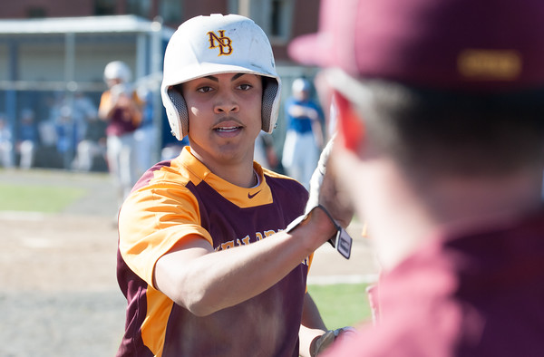 04/23/18 Wesley Bunnell | Staff New Britain baseball defeated Southington 9-8 in extra innings on Monday afternoon in a contest played at Southington High School. Melvin Rodriguez (6) high fives teammates and coaches after scoring a run.