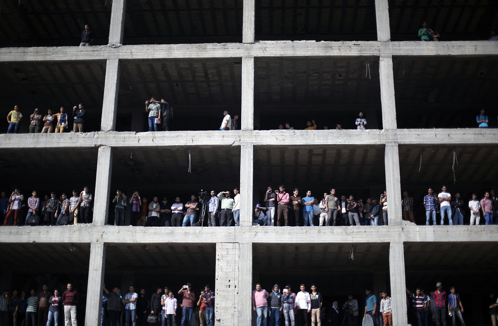 . Palestinians standing on a building under construction look at security forces during an anti-Israel on November 13, 2013 in the streets of Gaza City as part of the celebrations marking the first anniversary of Israel\'s Operation Pillar of Defense.   AFP PHOTO/MOHAMMED ABED/AFP/Getty Images