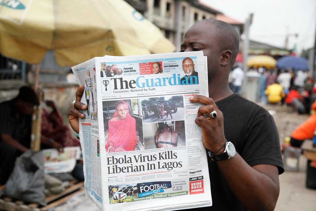 . A man reads a newspaper on a Lagos street with the headline Ebola Virus kills Liberian in Lagos, Saturday, July 26, 2014. An Ebola outbreak that has left more than 660 people dead across West Africa has spread to the continent\'s most populous nation after a Liberian man with a high fever vomited aboard an airplane to Nigeria and then died there, officials said Friday. The 40-year-old man had recently lost his sister to Ebola in Liberia, health officials there said. It was not immediately clear how he managed to board a flight, but he was moved into an isolation ward upon arrival in Nigeria on Tuesday and died on Friday. (AP Photo/Sunday Alamba)