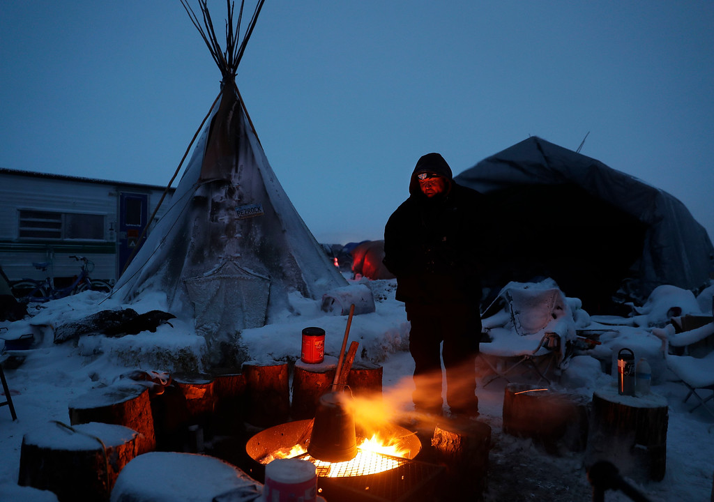 . James Logan, a Northern Arapaho Native American from Wyoming, warms himself by a fire next to his teepee at the Oceti Sakowin camp where people have gathered to protest the Dakota Access oil pipeline in Cannon Ball, N.D., Monday, Dec. 5, 2016. Another snowstorm was hitting the area Monday, and people in camp were busy shoring up housing and stockpiling firewood. (AP Photo/David Goldman)