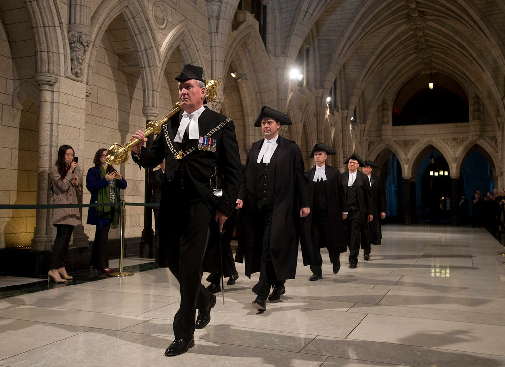 . Speaker of the House of Commons Andrew Scheer follows Sergeant-at-Arms Kevin Vickers through the Hall of Honour during the Speakers parade in the House of Commons Thursday, Oct. 23, 2014. Applause from all sides of the House rained down on Vickers as he entered the legislative chamber. Vickers was among those who opened fire on Michael Zehaf Bibeau, who stormed Parliament Hill on Wednesday. (AP Photo/The Canadian Press, Adrian Wyld)