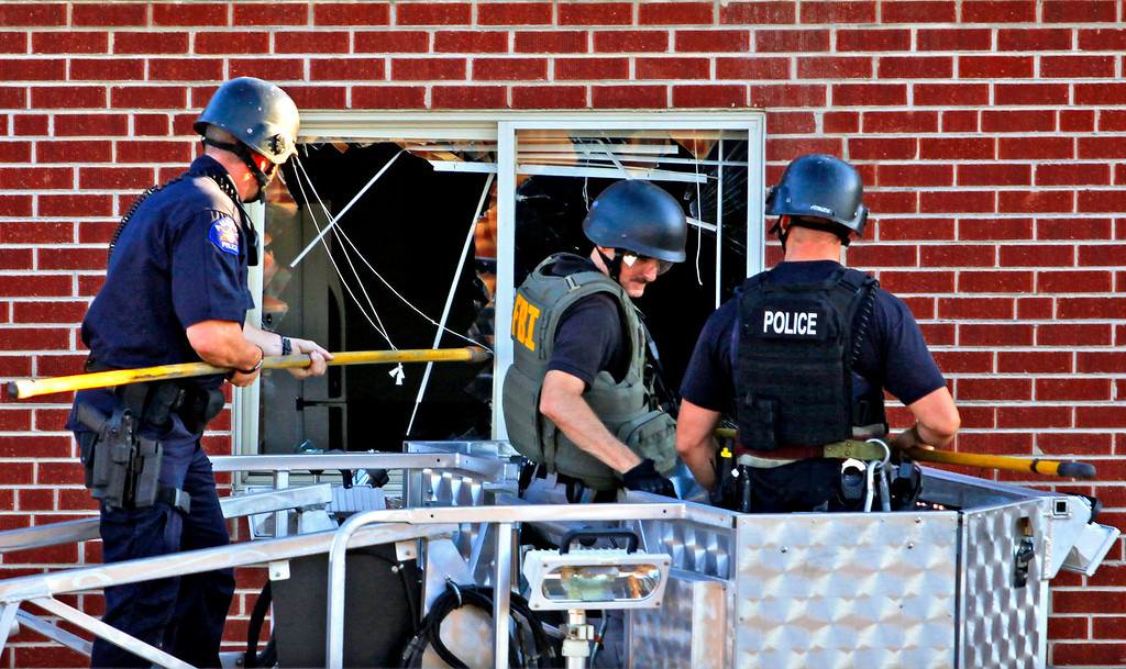 . Police investigate James Holmes\' apartment near the intersection of 17th Street and Paris Street on Friday, July 20, 2012. Holmes left a collection of explosives and gasoline-filled bottles in the apartment that would have incinerated parts of the building, hoping to distract police from the scene of the mass shooting at the movie theater. As he was arrested, Holmes told police there were explosives in his apartment. Law enforcement officers entered the apartment by breaking windows from a firefighting ladder bucket. Stephen Mitchell, The Denver Post