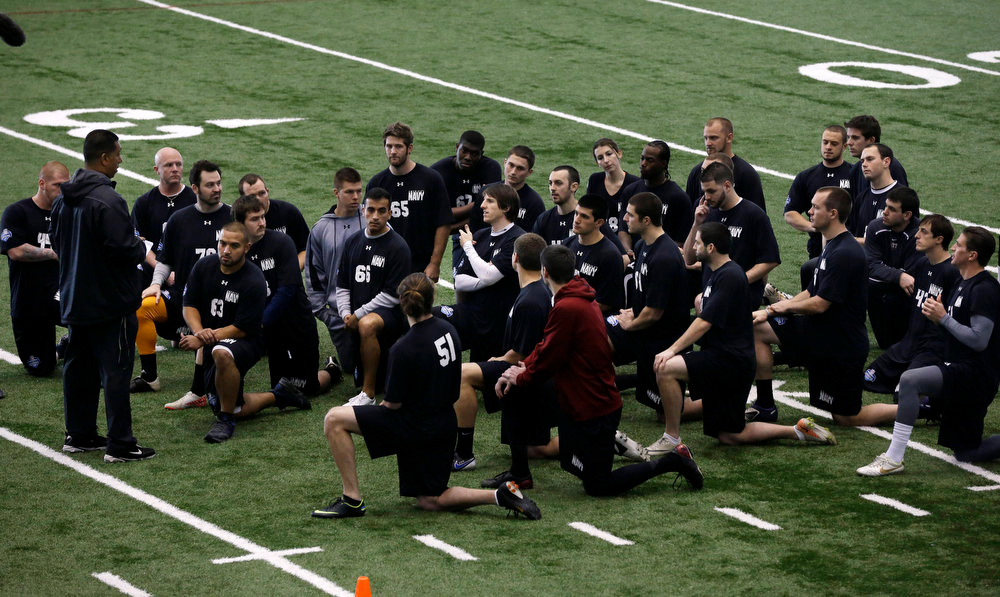 . Lauren Silberman, top center right, kneels on the indoor turf before kicker tryouts at the NFL football regional combine workout Sunday, March 3, 2013, in Florham Park, N.J. (AP Photo/Mel Evans)