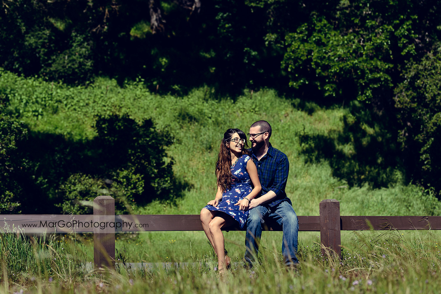 woman in blue dress and man in blue shirt sitting on the wooden fence during engagement session at Sunol Regional Wilderness