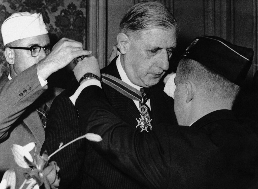 . 1958: Charles de Gaulle. General Charles de Gaulle is presented with the Gold Medal of the American Legion from Commander Russel Porter, President of the American Legion, back to camera, and Commander Carl J. Batter Jr., who fixes the ribbon, at a ceremony which took place in the Hotel Matignon in Paris, France on July 30, 1958. (AP Photo/POOL)