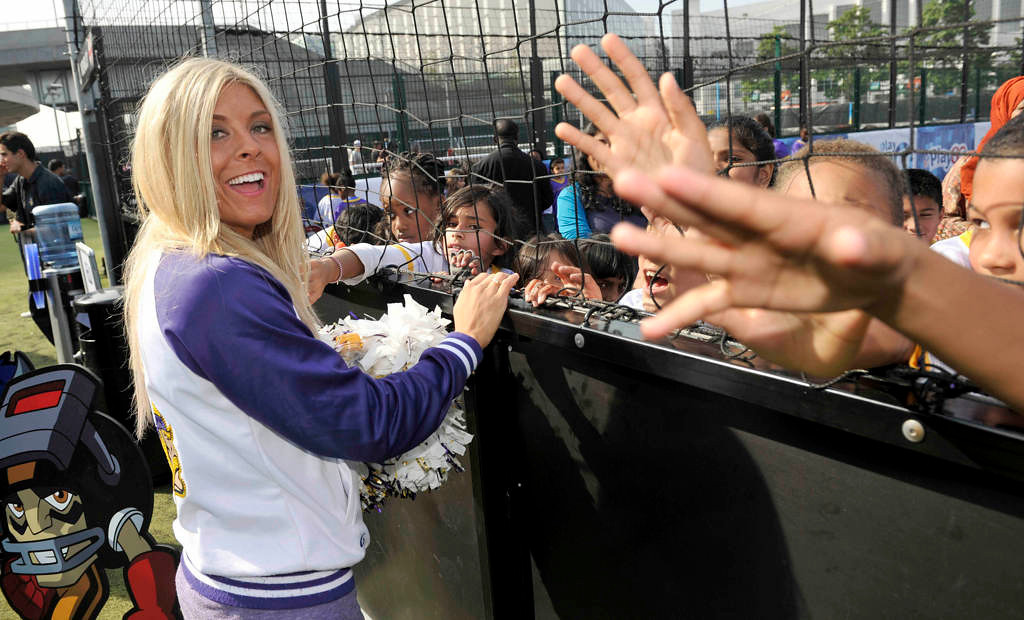 . A Minnesota Vikings cheerleader greets children at a football and cheerleading clinic with London children. (NFL: Sean Ryan)