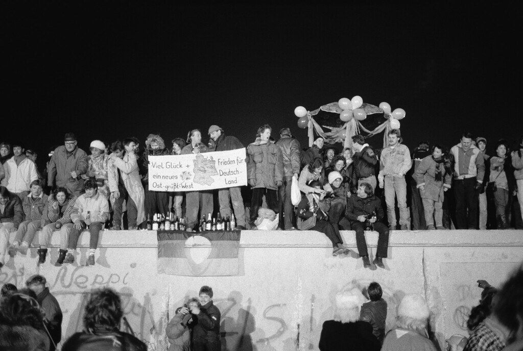 . A view from the east of Berliners gathered on the Berlin Wall to celebrate the New Year and the effective end of the city\'s partition, 31st December 1989. A banner reads \'Good luck and peace for a new Germany - East Greets West\'. (Photo by Steve Eason/Hulton Archive/Getty Images)