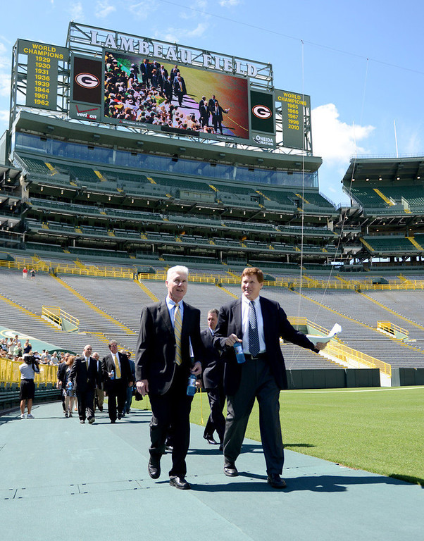 . Packers general manager Ted thompson, left, and president Mark Murphy walk onto the field for the annual shareholders meeting at Lambeau Field. (AP Photo/The Green Bay Press-Gazette, H. Marc Larson)