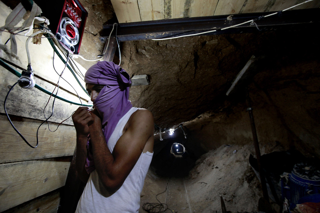 . In this Monday, Sept. 30, 2013 photo, a Palestinian works in a tunnel in Rafah, on the border between Egypt and the southern Gaza Strip. Since the summer, Egypt�s military has tried to destroy or seal off most of the smuggling tunnels under the Gaza-Egypt border, a consequence of the heightened tensions between Cairo and the Hamas government in Gaza. The tunnels once employed thousands of young men in Gaza. By early September, with most tunnels closed, only few tunnel workers reported to their jobs for maintenance work. Some mask their faces with shirts to avoid identification while working, for fear of repercussions in case they were to travel to Egypt in the future. (AP Photo/Hatem Moussa)