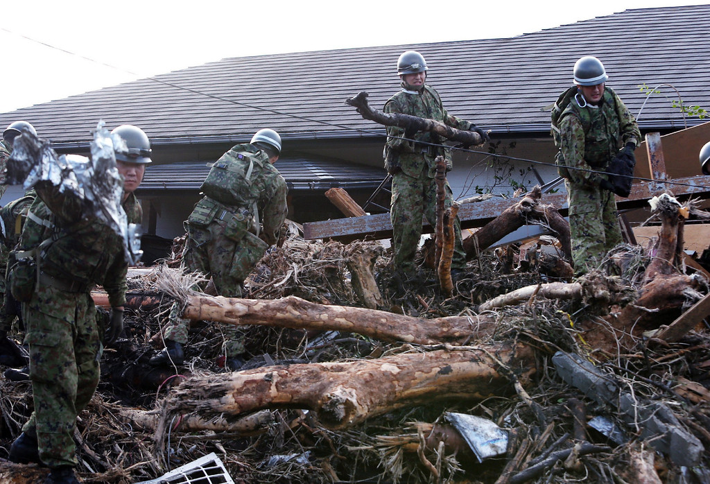 . Japan\'s Ground Self Defense Force soldiers remove debris to search for survivors after a landslide buried houses caused by heavy rain of typhoon Wipha at Oshima island, 120km south of Tokyo on October 16, 2013. At least 13 people are known to have died after a powerful typhoon lashed Japan\'s Pacific coast, warning that the death toll was likely to rise.  AFP PHOTO / JIJI PRESS /AFP/Getty Images