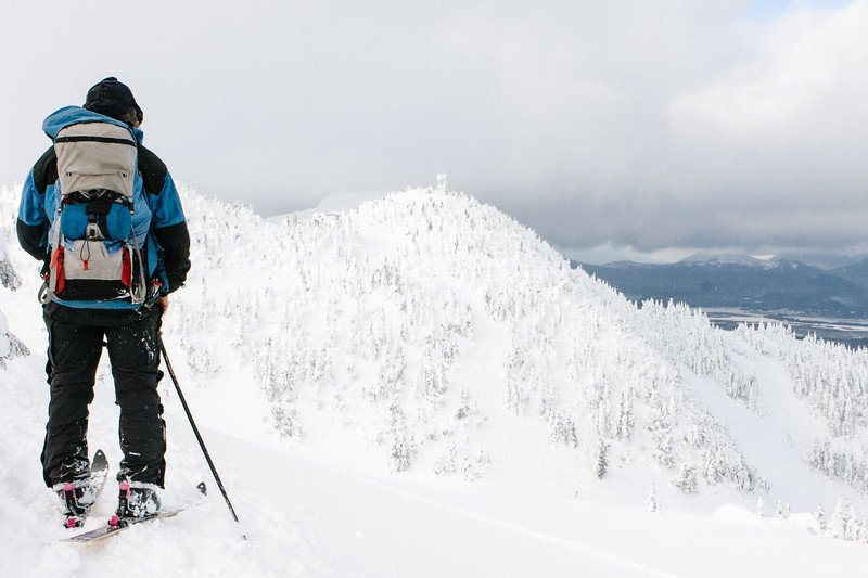 Man on skis going mountain camping in the winter