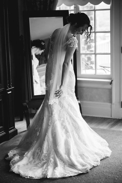The bride looking down at her flowing wedding dress  in front of a mirror.