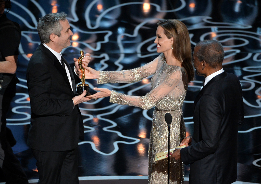 . (L-R) Director Alfonso Cuaron accepts the Best Achievement in Directing award for \'Gravity\' from actors Angelina Jolie and Sidney Poitier onstage during the Oscars at the Dolby Theatre on March 2, 2014 in Hollywood, California.  (Photo by Kevin Winter/Getty Images)