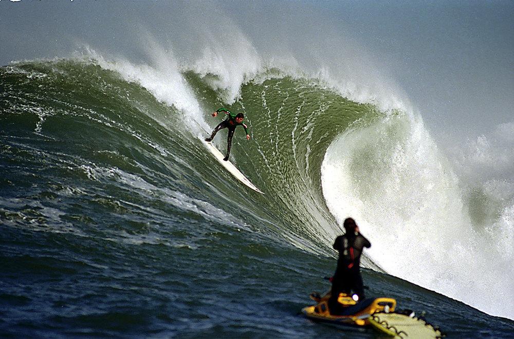 Description of . Peter Mel slides down a cliff in the 2000 Mavericks contest.  (Dan Coyoro/Sentinel)